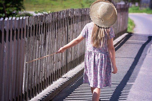 holčička u dřevěného plotu